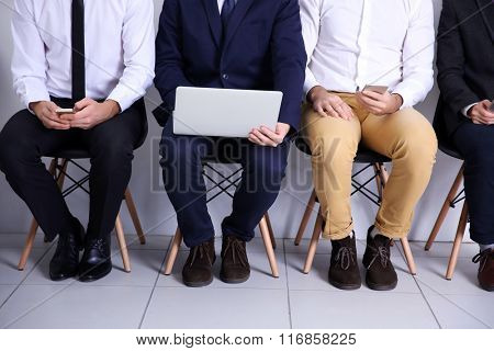 Young businessmen sitting on a chair and using devices in white hall, close up