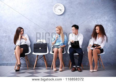 Young people sitting with briefcase on a chairs in grey hall