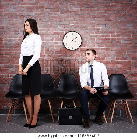 Young businessman and businesswoman waiting in brick wall hall