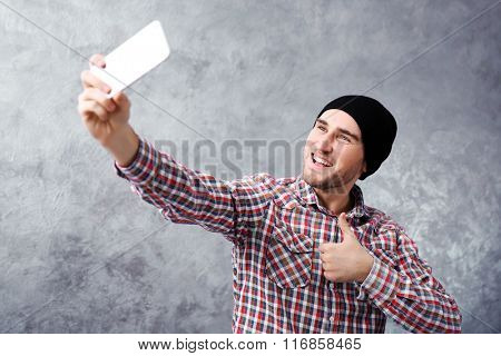 Young boy in black hat taking photo of him self with smart phone on grey wall background
