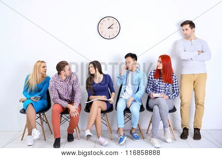 Young people sitting on a chairs in white hall