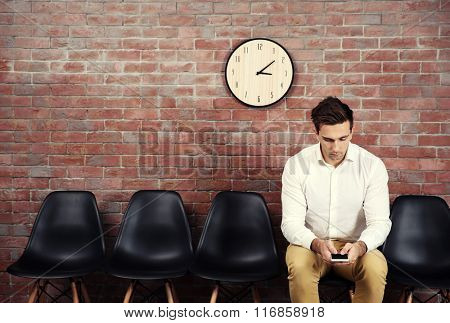 Young businessman sitting on a chair and using smart phone in brick wall hall