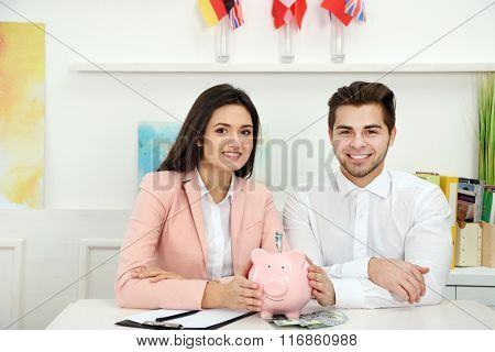 Happy young couple holding in hands piggy bank with dollar banknotes. Money savings concept