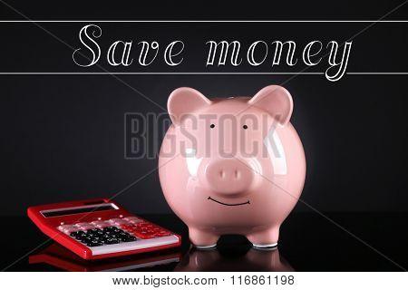 Piggy bank with calculator on dark background