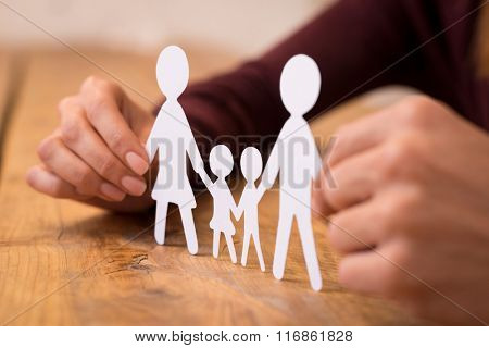 Close up of hands of a man and woman holding paper chain family. Young couple deciding on life after marriage. Closeup view of white paper cut family holding between hands.