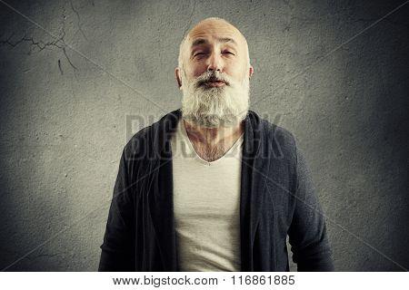 bearded senior man doing air kiss over dark background