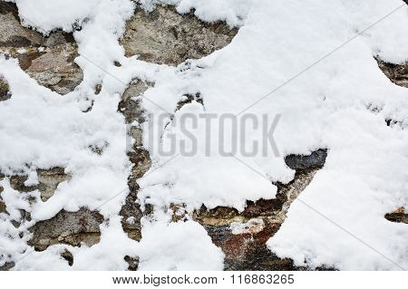 Winter season background of vintage stone wall texture with snow
