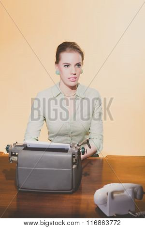 Distracted Retro 1950 Blonde Secretary Woman Sitting Behind Desk Working On Typewriter. High Angle V