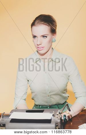 Distracted Vintage 1950 Blonde Secretary Woman Sitting Behind Desk Working On Typewriter. High Angle