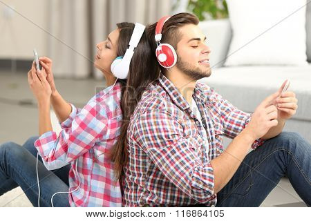 Teenager couple listening to music with headphones in living room