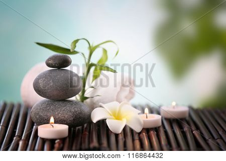 Spa stones with towel, candles and tropical flower on blurred background