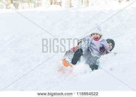 Two children sliding down snowy hill outdoors on orange plastic modern toboggan for kids