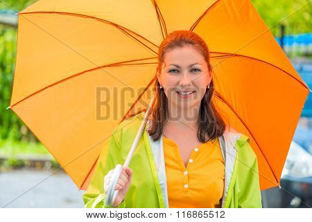 Portrait Of A Young Brunette With An Orange Umbrella Closeup