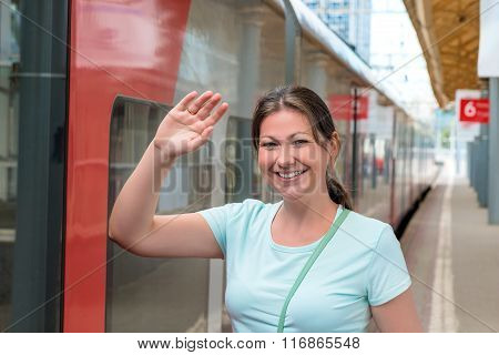 Young Woman Near A Train Welcomes Hand