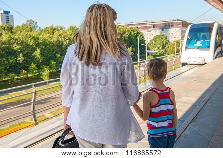 A Woman With A Child On The Platform Waiting For The Train