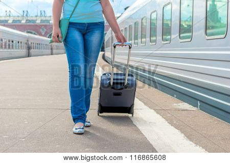 Girl In Jeans With A Suitcase Walking On Train Platform