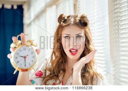 Beautiful happy smiling pinup woman showing alarm clock