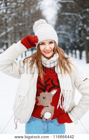 Young Beautiful Stylish Girl With Red Knitted Sweater With A Deer Walking In The Winter Garden