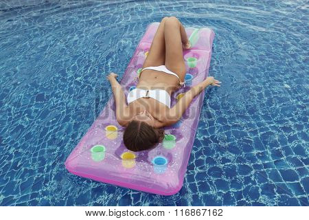 Close up view of an attractive young woman floating in swimming pool on waterbed