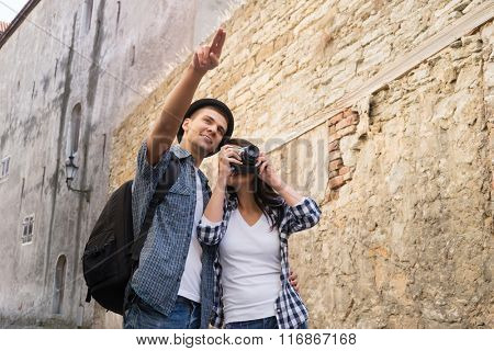 Traveling couple having a walk on bohemian street in Europe.