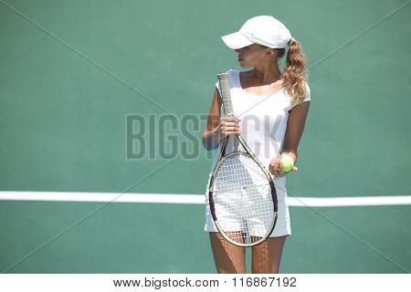 Young woman in white sportswear on tennis court