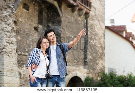 Young couple being tourists exploring the medieval buildings,