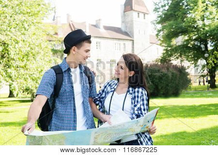 Traveling couple searching for their next destination with a map.