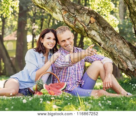 Lovely couple having a pleasant time eating fruits in the park.