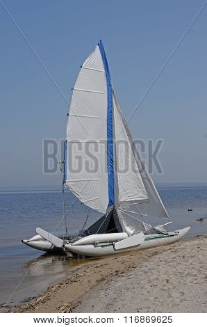 A lone sailboat on the sand on the beach.