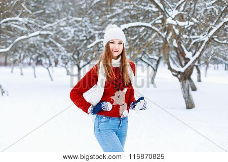 Beautiful Stylish Girl In A Knitted Cap, Red Sweater With A Deer And On A White Snowy Background Wit