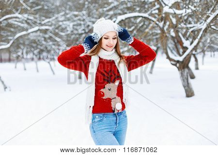 Pretty Woman In Red Knitted Sweater With A Deer Standing In A Winter Park.
