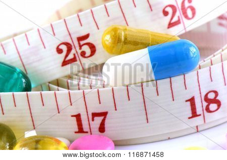 Medicine and Tape Measure on White Background in Waistline and Weight Control Concept.