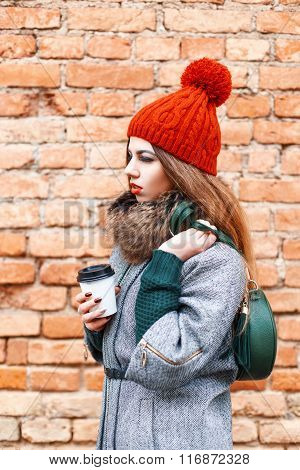 Young Fashion Model Girl Posing With Bag Of Coffee And A Warm Winter Clothes Near The Red Brick Wall