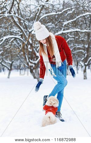 Beautiful Woman In Fashionable Knitwear Walking A Dog On The Background Of A Winter Park.