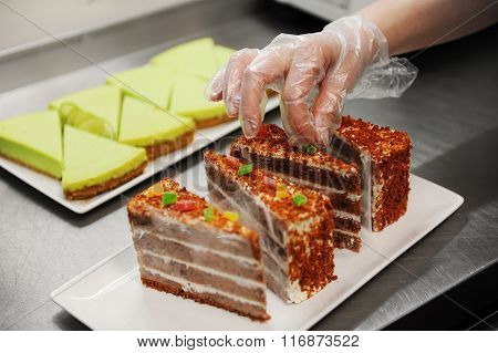 Confectioner is decorating chocolate cake