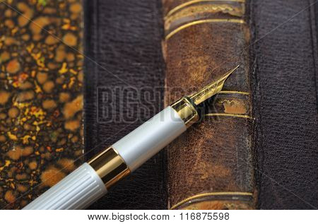 Fountain pen with a gold pen lying on old book closeup