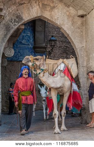Obidos; Portugal - August 09; 2015: Moorish man with dromedary camel in the parade of the Medieval Market reenactment. The Medieval Market festival is very popular among tourists.