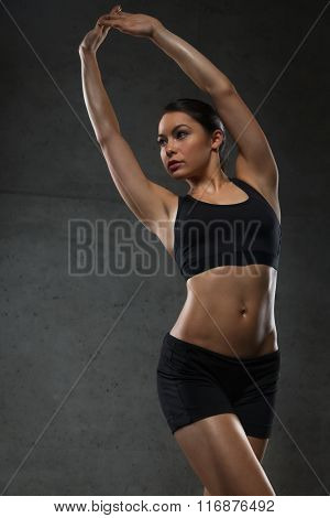 young woman posing and showing muscles in gym