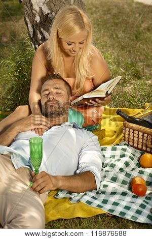 Happy blonde casual attractive woman reading for resting, handsome man after picnic. Smiling, high angle, outdoor.