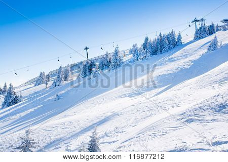 Vibrant panorama of the slopes at ski resort, snow trees, blue sky