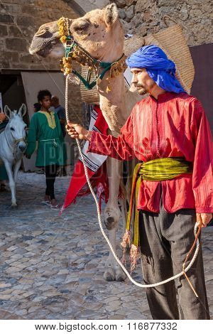 Obidos, Portugal - August 09, 2015: Moorish man with dromedary camel in the parade of the Medieval Market reenactment. The Medieval Market festival is very popular among tourists.