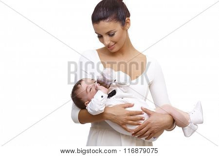 Happy young mother holding baby boy dressed in shirt and bow tie, drinking from feeding bottle.