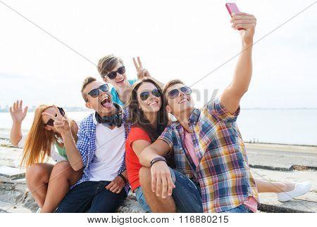 happy friends with smartphone taking selfie