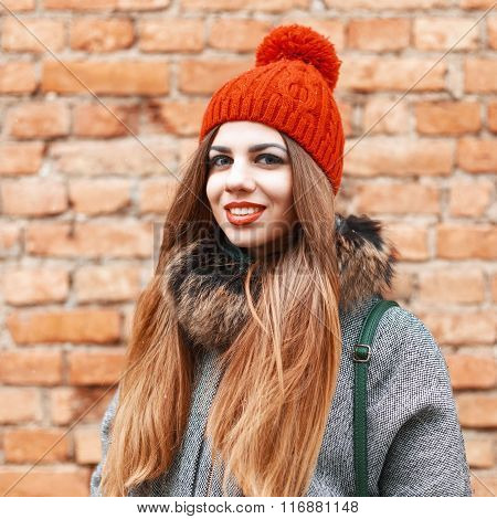 Beautiful Girl Smiling Near Brick Red Wall In Winter Day