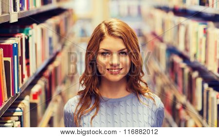 happy student girl or young woman in library