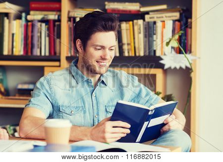happy student reading book and drinking coffee