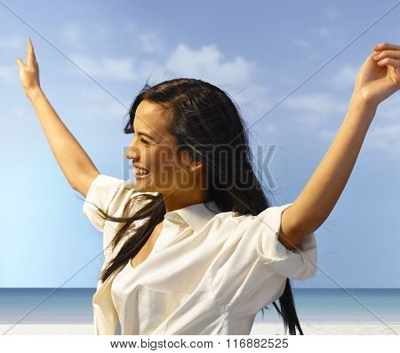 Attractive young woman enjoying summer holiday on the beach, laughing arms wide open.