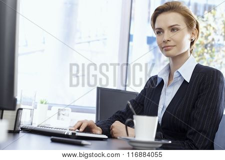 Attractive young businesswoman sitting at desk in bright office, typing on keyboard.