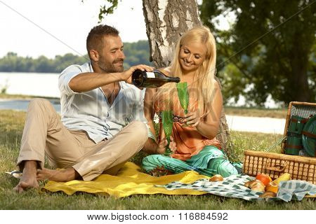 Happy casual handsome husband and blonde attractive wife drinking champagne at outdoor picnic. Smiling, sitting with basket, glasses and bottle, barefoot.