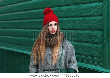 Beautiful Young Girl In Warm Clothes And Knit Cap Stands Near A Wooden House In The Village